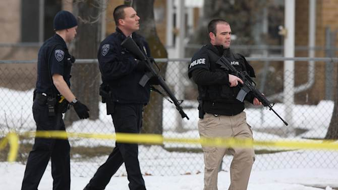 """Unified Police Department officers patrol a Midvale, Utah neighborhood after a shooting,  Tuesday, Feb. 12, 2013. Three people were shot to death and one was critically wounded at a known drug house in suburban Salt Lake City, causing temporary lockdowns at several area schools as police looked for two men who may have been involved. Investigators said a person inside the house reported the shooting in Midvale at about 8 a.m. Unified Police Department Lt. Justin Hoyal said a search warrant had been served at the house in recent weeks for drug activity. """"It was a known narcotics house,"""" he said. (AP Photo/The Deseret News, Ravell Call)  SALT LAKE TRIBUNE OUT;  MAGS OUT"""