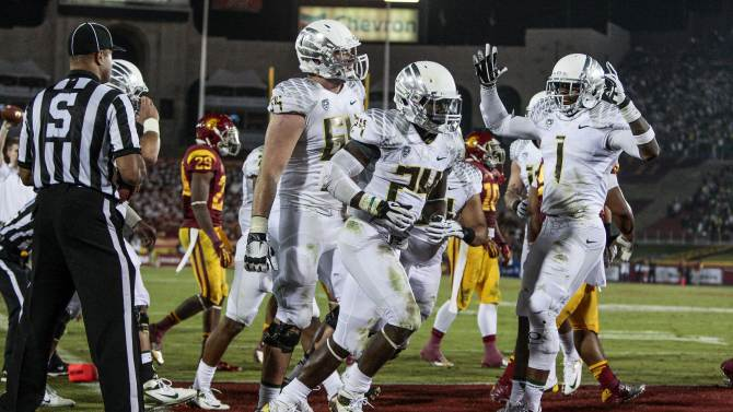 Oregon running back Kenjon Barner (24) celebrates scoring a touchdown during the second half of an NCAA college football game against the Southern California, Saturday, Nov. 3, 2012, in Los Angeles. Oregon won 62-51. (AP Photo/Bret Hartman)