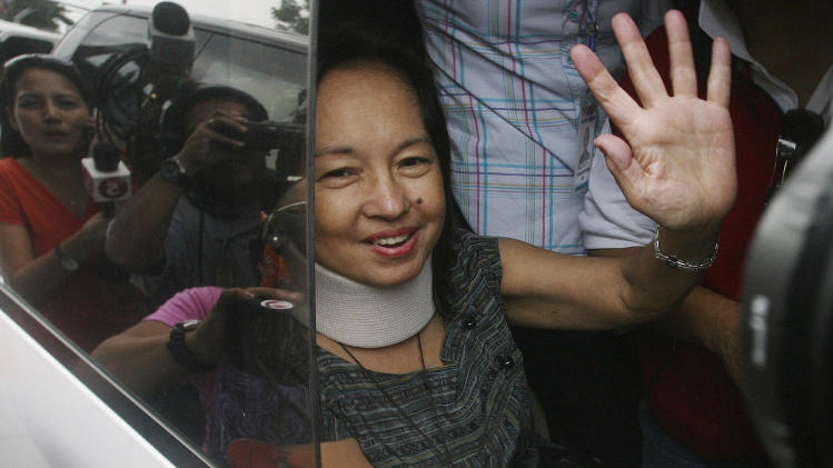 Former Philippine President Gloria Macapagal Arroyo waves to her supporters as she arrives at her village in suburban Quezon City, north of Manila, Philippines, Wednesday July 25, 2012. Arroyo on Wednesday walked out of a government hospital where she has been detained for nearly eight months on charges of election sabotage after a court found that evidence against her was weak and granted bail. (AP Photo)