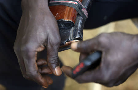 Leader of militia hunters helping the army to fight the Boko Haram insurgence in the northeast region of Nigeria, holds a magazine of bullets in his hands during an interview in Yola