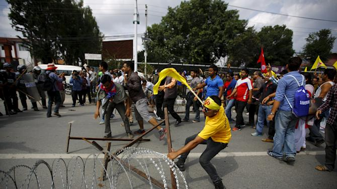 Hindu activists drag aside a barricade set up by police as they try to break into the restricted area near parliament during a protest demanding that Nepal be declared a Hindu state in the new constitution, in Kathmandu