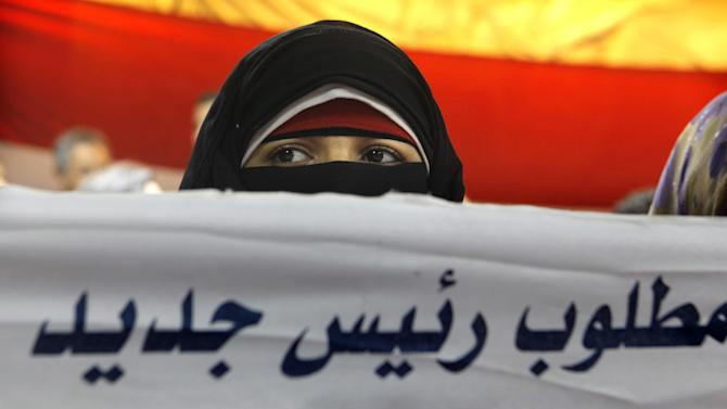 """A veiled Egyptian woman holds a banner with Arabic reading, """"we need a new president"""", during a press conference by the youth group leading the campaign against Egypt's president in Cairo, Saturday, June 29, 2013. Mahmoud Badr, a leader of the Tamarod, or rebel, movement said Saturday that 22,134,460 Egyptians have signed the petition demanding President Mohammed Morsi's ouster. (AP Photo/Amr Nabil)"""