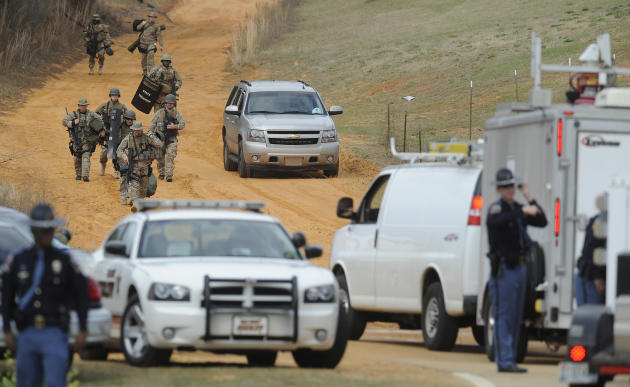 Heavily armed men move away from the suspects home at the scene of a Dale County hostage scene in Midland City, Ala. on Wednesday Jan. 30, 2013. Authorities were locked in a standoff Wednesday with a