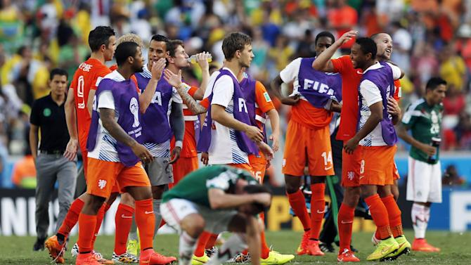 Dutch players celebrate after the World Cup round of 16 soccer match between the Netherlands and Mexico at the Arena Castelao in Fortaleza, Brazil, Sunday, June 29, 2014. The Netherlands won the match 2-1