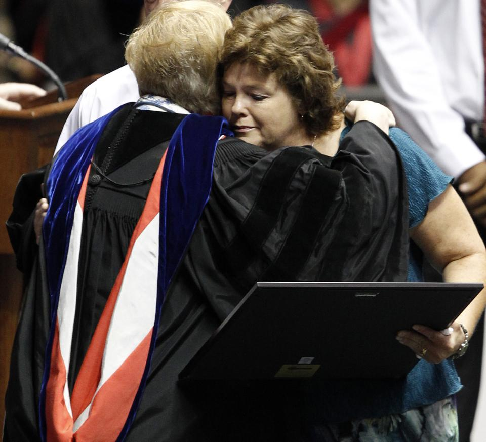 Vega Sigler hugs University Provost Dr. Judy Bonner as she accepts the degree from the University of Alabama on behalf of their daughter Morgan Sigler, Saturday, Aug. 6, 2011 in Tuscaloosa, Ala. Morgan lost her life when a tornado ripped through Tuscaloosa on April 27, 2011. (AP Photo/Butch Dill)