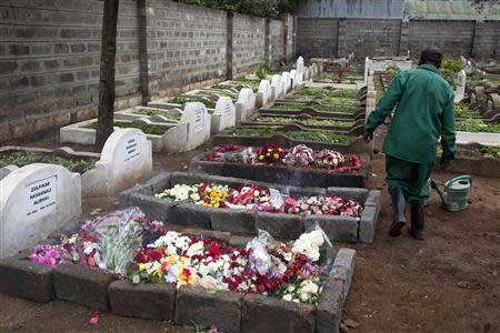 A cemetery worker walks near the fresh graves of Selima Merali and her daughter Nuriana Merali, who were killed in the attack by gunmen at the Westgate Shopping Centre in Nairobi