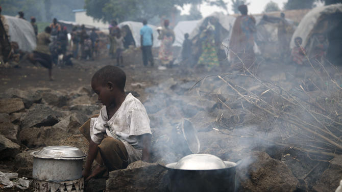 An internally displaced Congolese child  heats water at the Mugunga camp outside the eastern Congolese town of Goma, Saturday Nov. 24, 2012.  Regional leaders meeting in Uganda on Saturday called for an end to the advance by M23 rebels toward Congo's capital, and also urged the Congolese government to sit down with rebel leaders as residents fled some towns for fear of more fighting between the rebels and army.(AP Photo/Jerome Delay)