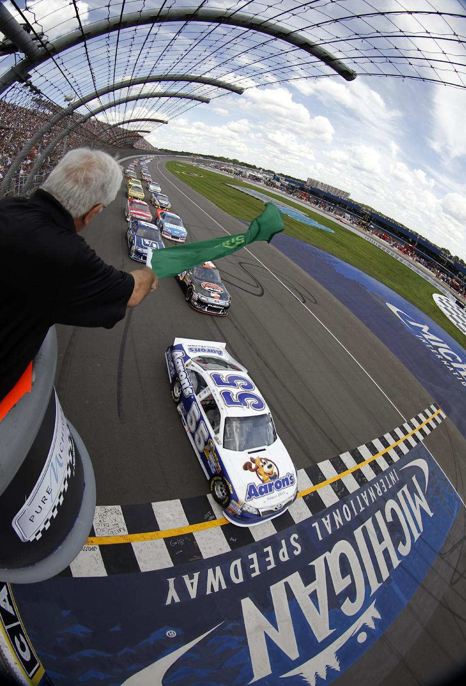 In this photo taken with a fisheye lens, Mark Martin (55) leads the field to the green flag to start the NASCAR Sprint Cup Pure Michigan 400 auto race at Michigan International Speedway, Sunday, Aug. 19, 2012, in Brooklyn, Mich. (AP Photo/Todd Warshaw, Pool)