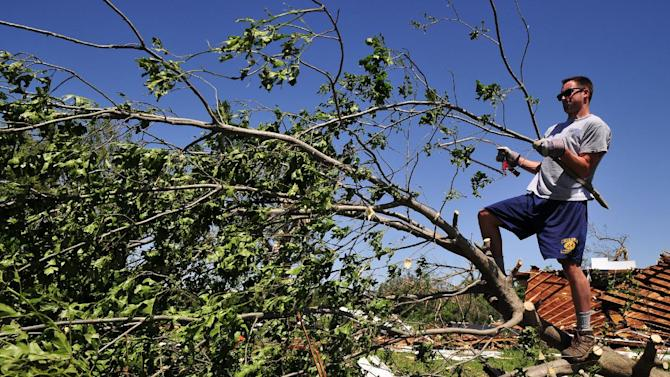 Josh Hill, a volunteer with Grace Chapel in Englewood, Colo., helps to clear downed branches from Angela and Wade Burleson's yard in El Reno Okla. on Saturday June 1, 2013 after their home was destroyed by one of the tornados that swept through Central Okla. on Friday. (AP Photo/Nick Oxford)