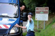 "A French gendarme points to a colleague on the ""Combe d'Ire"" road, in the French Alpine village of Chevaline where four people were found shot dead in a British-registered car"