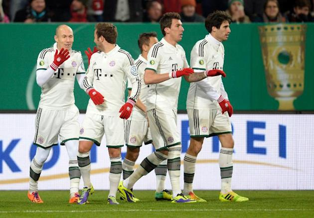 Bayern Munich's players celebrate scoring a goal during their German Cup match against Augsburg, in Augsburg, on December 4, 2013
