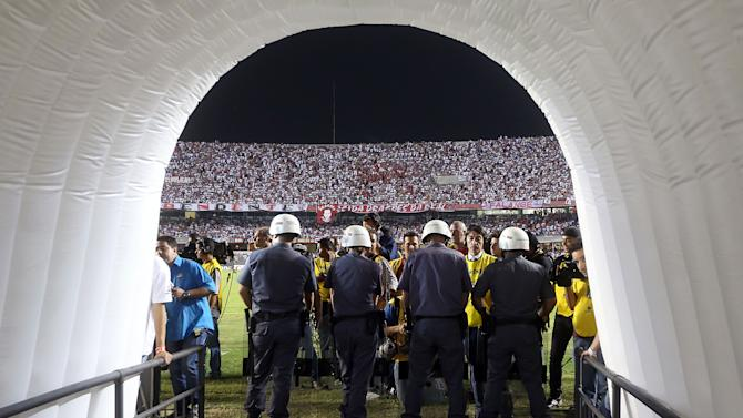 Police officers stand guard the entrance to Argentina's Tigre's dressing room after a fight among teams' members at the end of the first half of the Copa Sudamericana final soccer match against Brazil's Sao Paulo FC in Sao Paulo, Brazil, Wednesday, Dec. 12, 2012. (AP Photo/Andre Penner)