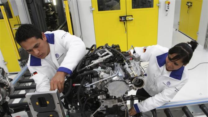 Technicians work on an engine during a media tour at the inauguration of Volkswagen's 100th plant worldwide in Silao
