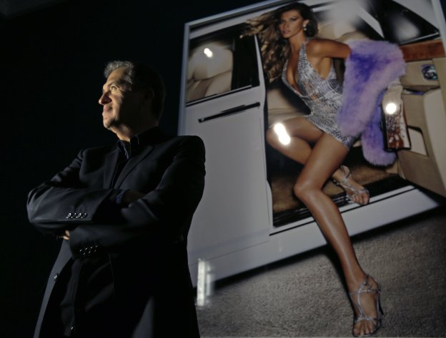"Photographer Mario Testino poses for a portrait during the preview of his shows ""In Your Face"" and ""British Royal Portraits"" at the Museum of Fine Arts in Boston, Wednesday, Oct. 17, 2012. At right is his image of Gisele Bundchen. (AP Photo/Charles Krupa)"