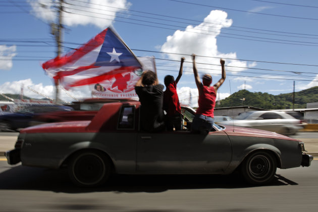 People ride atop a vehicle waving a Puerto Rican flag during elections in San Juan, Puerto Rico, Tuesday, Nov. 6, 2012. Puerto Ricans are electing a governor as the U.S. island territory does not get a vote in the U.S. presidential election. But they are also casting ballots in a referendum that asks voters if they want to change the relationship to the United States. A second question gives voters three alternatives: become the 51st U.S. state, independence, or sovereign free association, a designation that would give more autonomy. (AP Photo/Ricardo Arduengo)