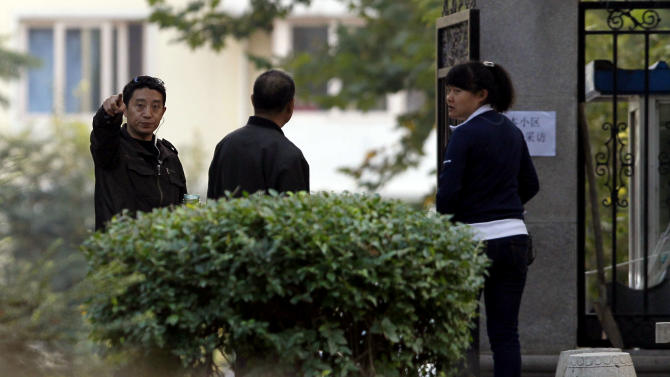 A plainclothes security officer gestures towards a photographer taking photos near the residential compound where Liu Xia, the wife of this year's Nobel Peace Prize winner Liu Xiaobo, is being held under house arrest in Beijing, China on Wednesday, Oct. 13, 2010.  The wife of the imprisoned Chinese dissident said she hopes to travel to Norway to collect the Nobel Peace Prize on his behalf, though for now she can only leave her Beijing home under police escort. (AP Photo/Ng Han Guan)