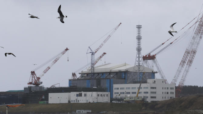 In this Nov. 9, 2012 photo, seagulls fly near the Oma nuclear power plant surrounded by cranes in Oma in Aomori, northern Japan. In nearby Oma, construction is set to resume on an advanced reactor that is not a fast-breeder but can use more plutonium than conventional reactors. Its construction, begun in 2008 for planned operation in 2014, has been suspended since the March 2011 Fukushima nuclear meltdowns, and could face further delays as Japan's new nuclear watchdog prepares new safety guidelines. (AP Photo/Koji Sasahara)