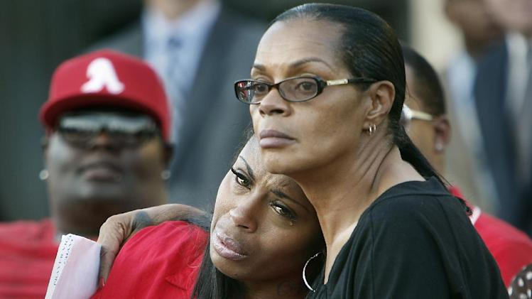 Teresa Carter, left, and Anne Carter Winters, mother and grandmother of Chavis Carter, comfort each other on Monday, Aug. 20, 2012 during a prayer vigil held on the grounds of The National Civil Rights Museum in Memphis, Tenn., for Chavis Carter, who Jonesboro, Arkansas, police say committed suicide while handcuffed. (AP Photo/The Commercial Appeal, Stan Carroll)