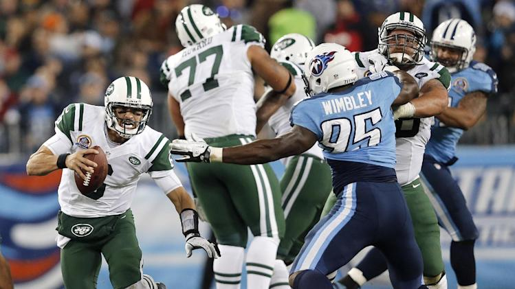 New York Jets quarterback Mark Sanchez (6) scrambles away from Tennessee Titans defensive end Kamerion Wimbley (95) in the second quarter of an NFL football game, Monday, Dec. 17, 2012, in Nashville, Tenn. (AP Photo/Joe Howell)