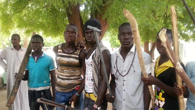 "In this photo taken with a mobile phone Tuesday, June 11, 2013, Vigilantes youths pose for a photographs in Maiduguri, Nigeria. As soldiers continue an offensive against radical Islamic extremists in northeast Nigeria, young men armed with machetes and sticks have now entered the streets of the region's biggest city, targeting suspected fighters. The members of the ""Civilian JTF,"" a play off the acronym used to describe the joint military and police taskforce in the region, already have come under attack from extremists for pointing out suspects to soldiers. However, it remains unclear what happens to those the group points out, as some suspects in Maiduguri have already been shot dead by security forces and left rotting in ditches in the city. (AP Photo/Abdulkareem Haruna)"