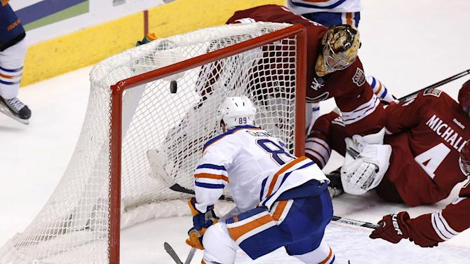 Edmonton Oilers' Sam Gagner (89) scores a goal as Phoenix Coyotes' Thomas Greiss, of Germany, top right, is caught behind the net during the third period of an NHL hockey game, Friday, April 4, 2014, in Glendale, Ariz.  The Oilers defeated the Coyotes in a shootout, 3-2