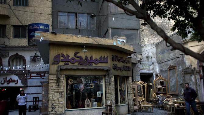 """In this Thursday, Jan. 3, 2013 photo, A man, right, walks past an instrument shop with Arabic that reads, """"fine art shop, musical instruments, Samir Hamido,"""" on Mohammed Ali street, a street modeled after Paris' boulevards, home to musicians, belly-dancers and instrument makers, in downtown Cairo, Egypt. Parts of the street lined by French-style arched arcades, are now dominated by mobile phone and electronics stores, donkey carts and heavy traffic. The shops making, repairing and selling musical instruments that once packed the street are disappearing, along with their window displays of lute-like, stringed ouds, qanouns  and tablas a drum made equally for the rapid-fire hand beats of belly-dance tunes or for the languid rhythms of a love ballad by Umm Kalthoum, the most famed singer of classical Arabic music. (AP Photo/Nasser Nasser)"""