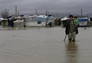 A Syrian refugee man carries his baby as he makes his way through flooded water at a temporary refugee camp, in the eastern Lebanese Town of Al-Faour near the border with Syria, Lebanon, Tuesday, Jan. 8, 2013. Two Syrian refugee encampments in Lebanon's eastern Bekaa valley were completely immersed in water Tuesday after the Litani river flooded and the water came pouring into their tents. The flood forced dozens of Syrian refugees to leave in search for alternative shelter along with their water-soaked and muddied belongings. (AP Photo/Hussein Malla)