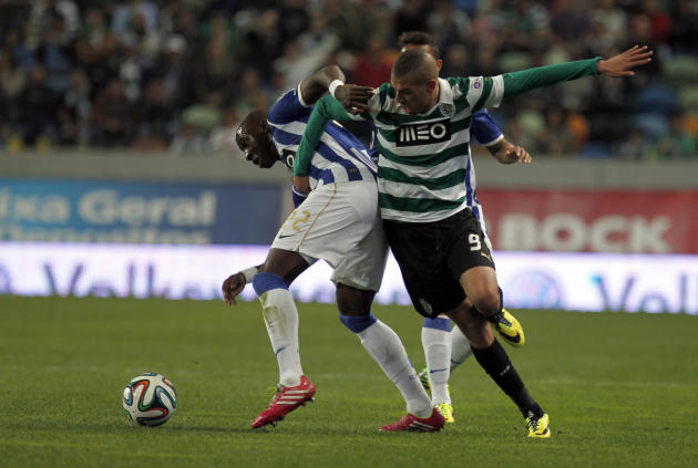 Sporting's Islam Slimani, right, from Algeria, battles for the ball with Porto's Eliaquim Mangala, from France, during the Portuguese league soccer match between Sporting and Porto at Sporting