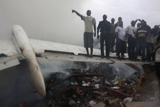 People gather at the site of a plane crash in Lagos, Nigeria, Sunday, June 3, 2012. A passenger plane carrying more than 150 people crashed in Nigeria's largest city on Sunday, government officials sa