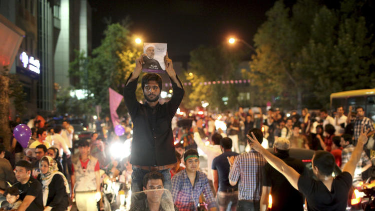 A supporter of Iranian presidential candidate Hasan Rowhani holds up his poster while celebrating Rowhani's victory, in Tehran, Iran, Saturday, June 15, 2013. Wild celebrations broke out on Tehran streets that were battlefields four years ago as reformist-backed Rowhani capped a stunning surge to claim Iran's presidency on Saturday, throwing open the political order after relentless crackdowns by hard-liners to consolidate and safeguard their grip on power. (AP Photo/Ebrahim Noroozi)