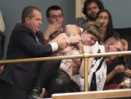 A topless Femen activist is carried out of the legislature visitor section by security after protesting the presence of the crucifix inside the legislature in Quebec City on Tuesday, October 1, 2013. THE CANADIAN PRESS/Jacques Boissinot