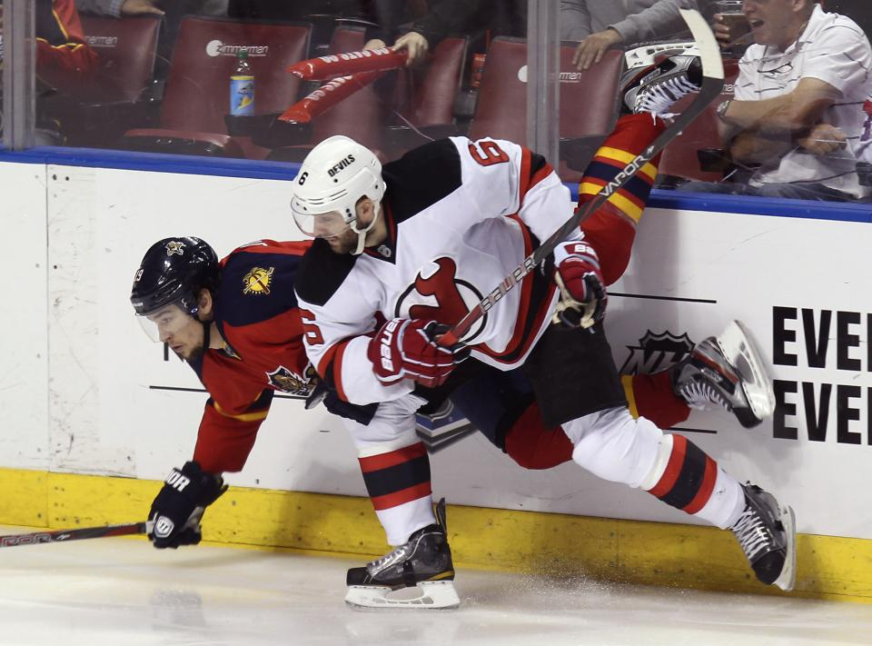 New Jersey Devils' Andy Greene (6) upends Florida Panthers' Scottie Upshall during the third period of Game 7 in a first-round NHL Stanley Cup playoff hockey series, in Sunrise, Fla., Wednesday, April 26, 2012. (AP Photo/J Pat Carter)