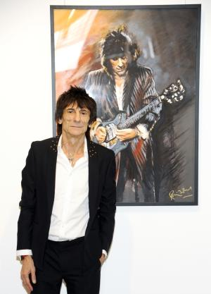 "Rolling Stones guitarist Ronnie Wood stands near one of his pieces during a news conference unveiling his new art exhibit ""Faces, Time and Places"" on Monday, April 9, 2012, in New York. (AP Photo/Evan Agostini)"