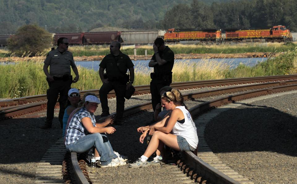 Union workers sit on railroad tracks to block a grain train, in background,5 as police stand by in Longview, Wash.,  Wednesday, Sept. 7, 2011.   Longshoremen  blocked the train as part of an escalating dispute about labor at the EGT grain terminal at the Port of Longview.(AP Photo/Don Ryan)