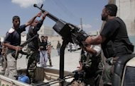 Syrian rebel fighters stand around an anti-aircraft machinegun mounted on a truck in the northern city of Aleppo. Rebel-held quarters of Syria's Aleppo have come under heavy bombardment by regime forces, as a senior security official said the real battle for control of the strategic northern city was yet to come