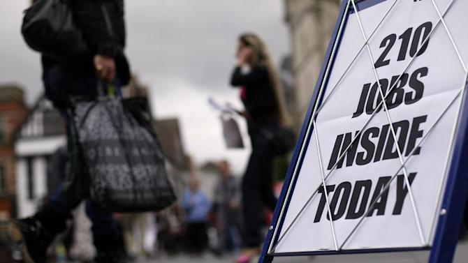 Shoppers walk past a newspaper advertising board promoting its job supplement in Leicester, central England