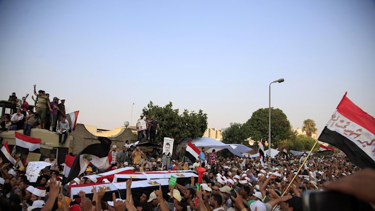 Supporters of Egypt's ousted President Mohammed Morsi carry coffins, covered with the national flag, of four men killed after Egyptian troops opened fire on mostly Islamist protesters marching on a Republican Guard headquarters Friday, in Cairo, Saturday, July 6, 2013. (AP Photo/Khalil Hamra)