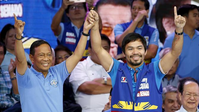 Philippine Vice President Jejomar Binay and Filipino boxer Manny Pacquiao make their political party sign during the start of campaigning for the national elections in Manila