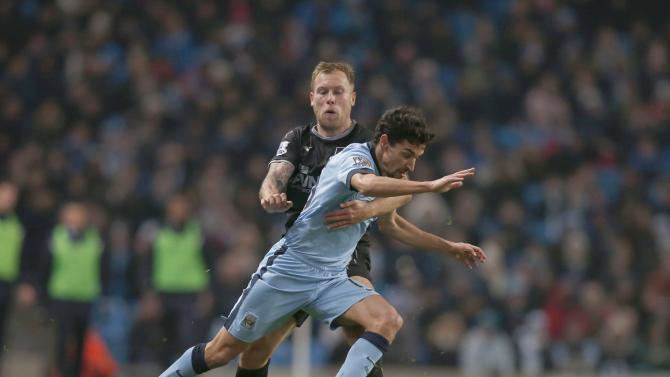 Burnley's Scott Arfield challenges Manchester City's Jesus Navas during their English Premier League soccer match at the Etihad Stadium in Manchester