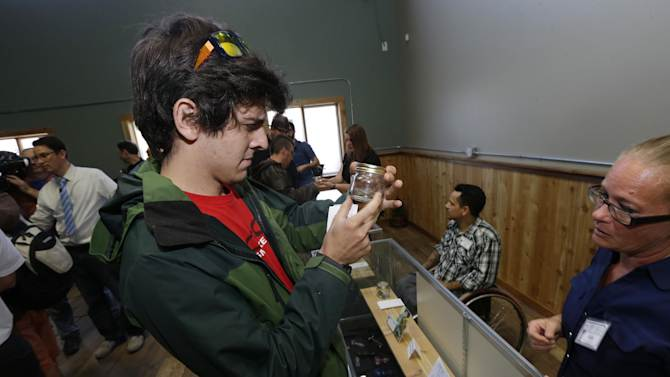 "Sam Pyle, left, inspects a ""sniff jar"" containing a sample of recreational marijuana at Top Shelf Cannabis, Tuesday, July 8, 2014, in Bellingham, Wash., on the first day of legal sales in the state. (AP Photo/Ted S. Warren)"