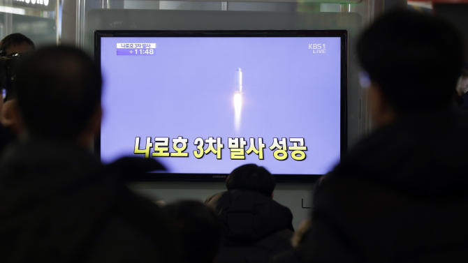 "South Koreans watch a television broadcast reporting the country's first rocket launch at Seoul Railway Station in Seoul, South Korea, Wednesday, Jan. 30, 2013. South Korea has launched a rocket in its third attempt to place a satellite in space from its own soil. The writing reads "" Success third attempt."" (AP Photo/Lee Jin-man)"