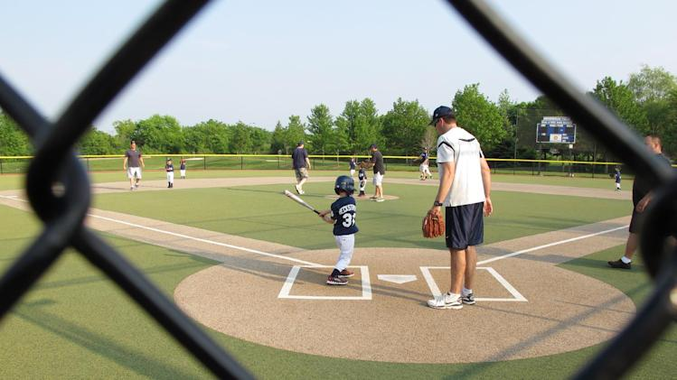 A young batter takes a swing as a father who's a coach supervises at a youth baseball game in Buffalo Grove, Ill. on Monday June 10, 2013. Earlier in the month, park district officials in the Chicago suburb posted signs asking parents to behave and keep the games in perspective. (AP Photo/Martha Irvine)
