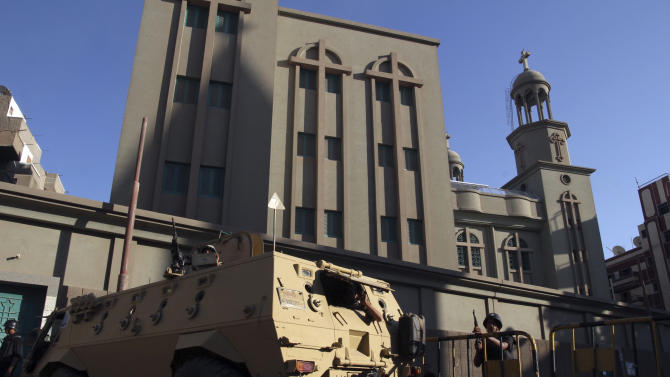 In this Sunday, Aug. 18, 2013 photo, an Egyptian armored vehicle and army soldiers stand guard outside the main Christian Orthodox Cathedral in the southern city of Assiut, Egypt. In the five days since security forces cleared two sit-in camps by supporters of Egypt's ousted president, Islamists have attacked dozens of Coptic churches along with homes and businesses owned by the Christian minority. The campaign of intimidation appears to be a warning to Christians outside Cairo to stand down from political activism. (AP Photo/Roger Anis, El Shorouk Newspaper) EGYPT OUT