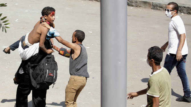 Egyptian protesters evacuate an injured youth toward a waiting ambulance, unseen, during clashes with security forces, unseen by the street leading to the U.S. embassy in Cairo, Egypt, Friday, Sept. 14, 2012, as part of widespread anger across the Muslim world about a film ridiculing Islam's Prophet Muhammad. (AP Photo/Nasser Nasser)
