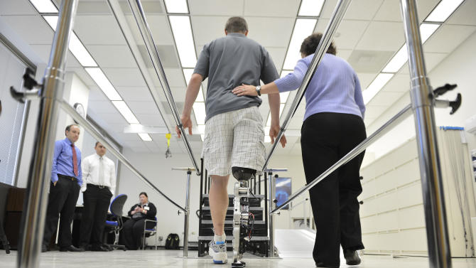 """Physical therapist assistant Suzanne Finucane, right, helps Zac Vawter as he practices walking with an experimental """"bionic"""" leg at the Rehabilitation Institute of Chicago, Thursday, Oct. 25, 2012 in Chicago.  Vawter will put his bionic leg to the ultimate test Sunday, Nov. 4,  when he attempts to climb 103 flights of stairs to the top of Chicago's Willis Tower, one of the world's tallest skyscrapers. If all goes well, he'll make history with the bionic leg's public debut.  (AP Photo/Brian Kersey)"""
