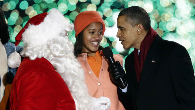 President Barack Obama, right, and daughter Malia Obama, sing as Santa Claus arrives during the 90th annual National Christmas Tree Lighting ceremony on the Ellipse south of the White House, Thursday, Dec. 6, 2012, in Washington. (AP Photo/Alex Brandon)