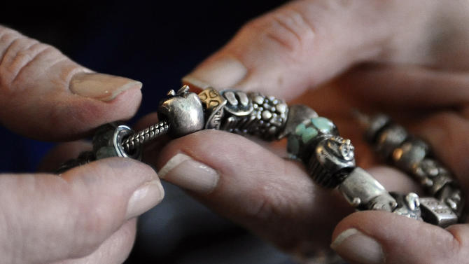 In this Tuesday, Feb. 5, 2013 photo, Teresa Rousseau points out an apple charm on a bracelet worn by her daughter, teacher Lauren Rousseau on the day she was killed during an interview at her home in Danbury, Conn. Lauren Rousseau, 30, was one of 26 people killed in the Dec. 14, 2012 massacre at Sandy Hook Elementary School in Newtown, Conn.  Lauren Rousseau will be one of six educators from the school honored posthumously with the 2012 Presidential Citizens Medal, presented at a White House ceremony on Feb. 15. (AP Photo/Jessica Hill)