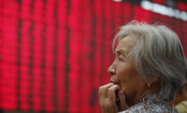 An investor looks at the stock price monitor at a private securities company Thursday Sept. 27, 2012 in Shanghai, China. Most Asian stocks moved modestly higher Thursday as investors positioned themselves ahead of major holiday that will shut markets in Hong Kong and mainland China next week. (AP Photo)