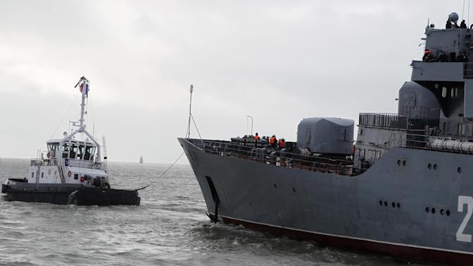 """The Russian navy ship Smolny, right, with about 400 Russian sailors aboard,  is being tugged out of the port of Saint-Nazaire western France, Thursday, Dec.18, 2014. Russian sailors are leaving the French Atlantic port without the controversial French-made warship they were supposed to sail away on. France suspended the delivery of the ship to Russia """"until further notice"""" last month because of the conflict in Ukraine. (AP Photo/Laetitia Notarianni)"""
