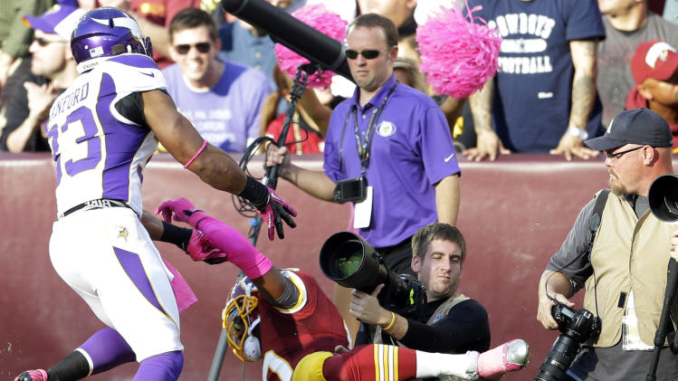 Washington Redskins quarterback Robert Griffin III is pushed into a photographer after being hit by Minnesota Vikings safety Jamarca Sanford (33) during the first half of an NFL football game, Sunday, Oct. 14, 2012, in Landover, Md. (AP Photo/Pablo Martinez Monsivais)